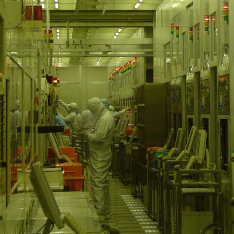 Teams of engineers adjusting systems at the CVD process bay but only one green lamp is on, indicating a system is operating. (At the 200mm line in the Naka clean room)